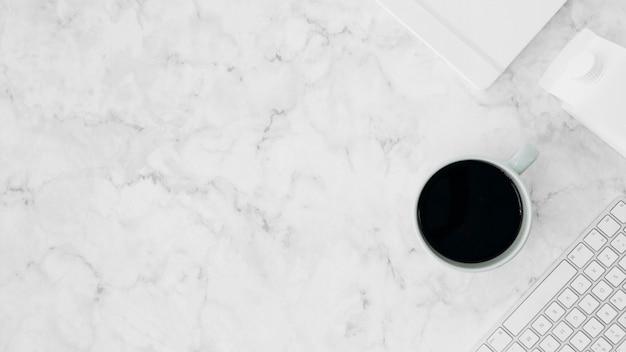 Karton mleka; klawiatura; filiżanka kawy i pamiętnik na białym tle marmuru