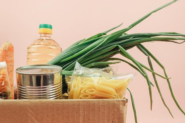 Karton na białym tle na różowym tle z masłem, konserwami, cebulą, ciastkami, makaronem, owocami. dostawa jedzenia.