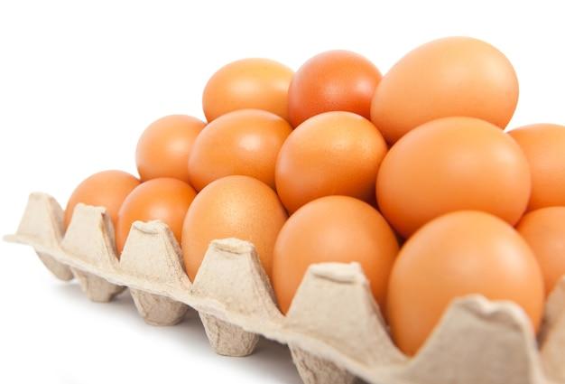 Karton świeżych jaj brązowy na białym tle.