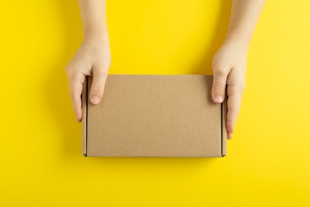 Karton w ręce dziecka na żółtym tle, widok z góry.