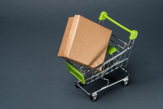 Karton w wózku na zakupy w kolorze szarym. skopiuj miejsce