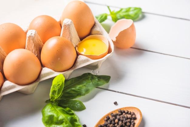 Karton z jajami; liść bazylii i pieprzu na drewnianej desce