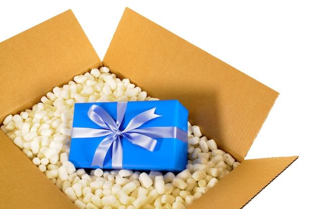 Karton z niebieskim prezentem i kawałkami styropianu.