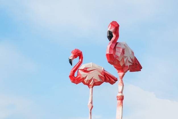Kartonowa dekoracja flamingo przeciw niebieskiemu niebu.
