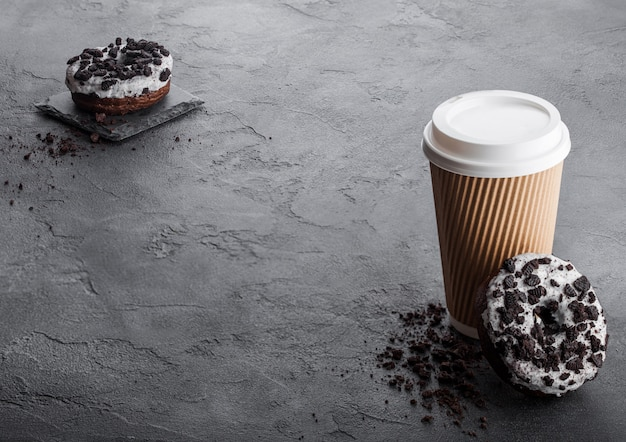 Kartonowa filiżanka kawy z czarnymi ciastkami pączkami na czerń kamienia kuchennym stole. napój w kawiarni i przekąska.