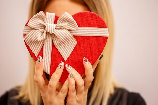 Kartonowe biodegradowalne pudełko w kształcie serca w rękach kobiet