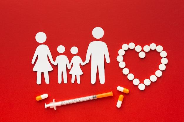 Kartonowe kształty rodzinne z lekami i strzykawką