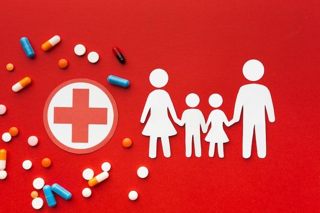 Kartonowe kształty rodzinne z lekami i symbolem czerwonego krzyża