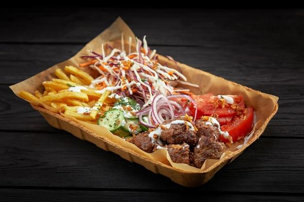 Kartonowe pudełko wypełnione potrawami z grilla: kebab, warzywa, frytki, sos pomidorowy i majonezowy