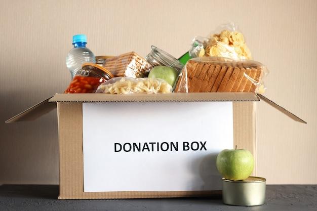 Kartonowe pudełko z darami żywności na zbliżenie stołu table