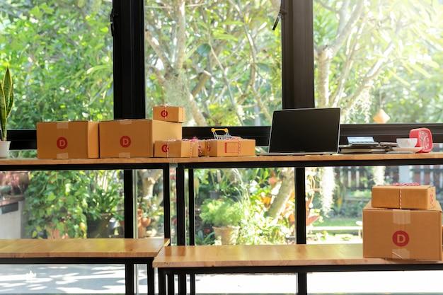 Kartonowe pudełko z paczkami i laptop na biurku.
