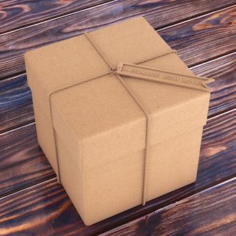 Kartonowe pudełko ze sznurkiem i drewnianą zawieszką z napisem handmade with love na drewnianym stole. renderowanie 3d