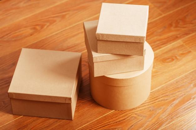 Kartonowe skrzynki pocztowe na drewnianej podłodze o różnych kształtach.