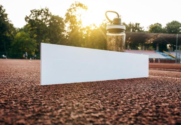 Kartonowy biały talerz z butelką wody na tle bieżni