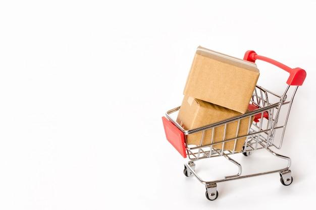 Kartony lub papierowi pudełka w czerwonym wózek na zakupy na białym tle. z miejsca na kopię