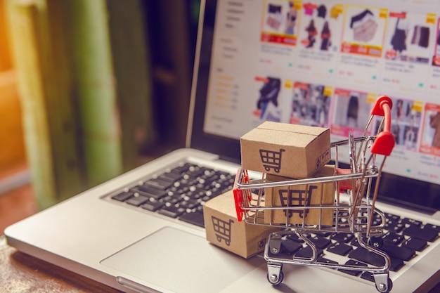 Kartony paczkowe lub papierowe z logo koszyka na zakupy w wózku na klawiaturze laptopa