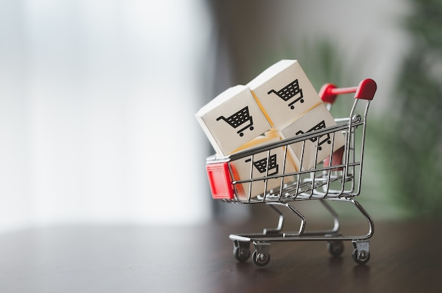 Kartony papierowe z logo koszyka na wózku do dostawy. zakupy online lub koncepcja marketingu i handlu