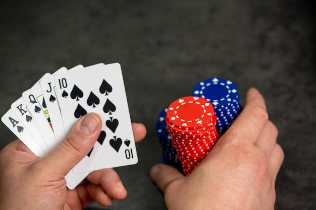 Karty do gry i żetony osiągają szczyt koloru na szarym tle cementu