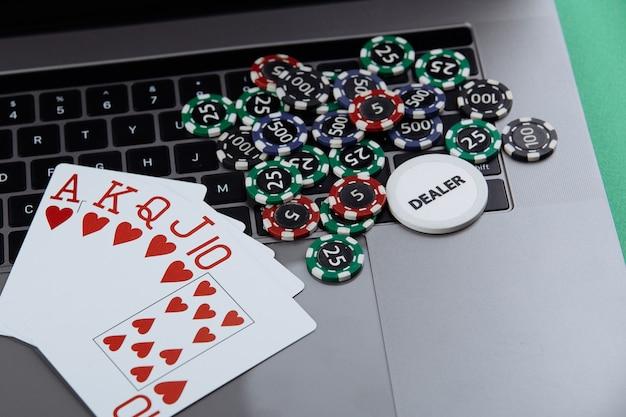 Karty do pokera i stosy żetonów pokerowych na komputerze przenośnym. koncepcja online pokera.