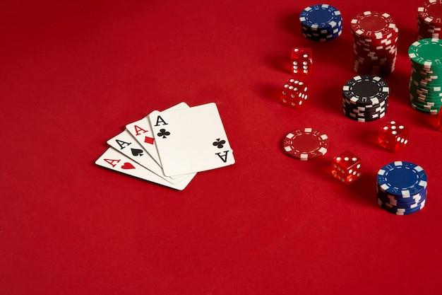 Karty do pokera i żetony do gry na czerwonym tle. widok z góry. skopiuj miejsce. martwa natura. leżał płasko. karty - cztery asy. 4 w swoim rodzaju