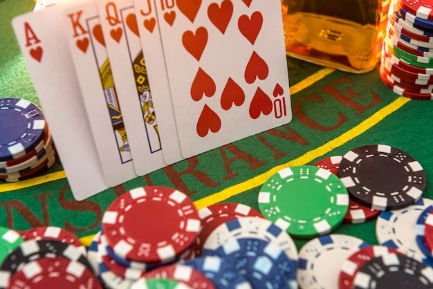Karty do pokera i żetony do kasyna przy whisky na zielonym stole pokerowym
