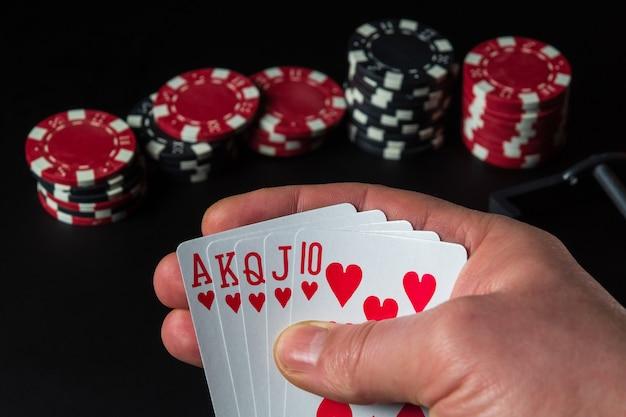 Karty do pokera z kombinacją pokera królewskiego. zbliżenie dłoni gracza z kartami do gry w kasynie