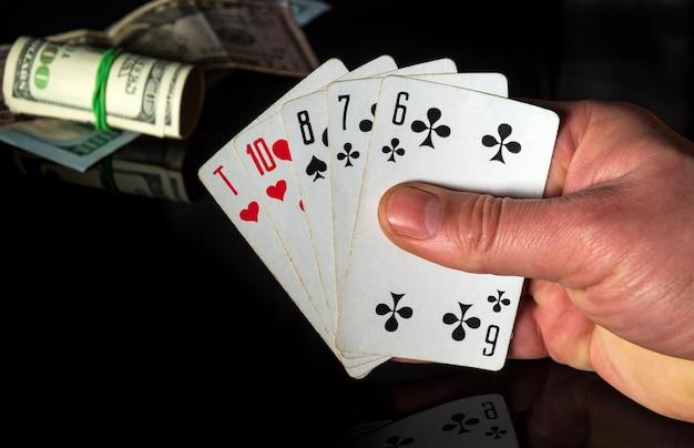Karty do pokera z wysoką kombinacją kart. zbliżenie dłoni hazardzista trzyma karty do gry w kasynie