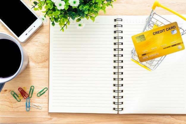 Karty kredytowe, notatnik, doniczka, smartfon, wózek na zakupy i filiżanka kawy na drewnianym tle, bankowość internetowa widok z góry stół biurowy.