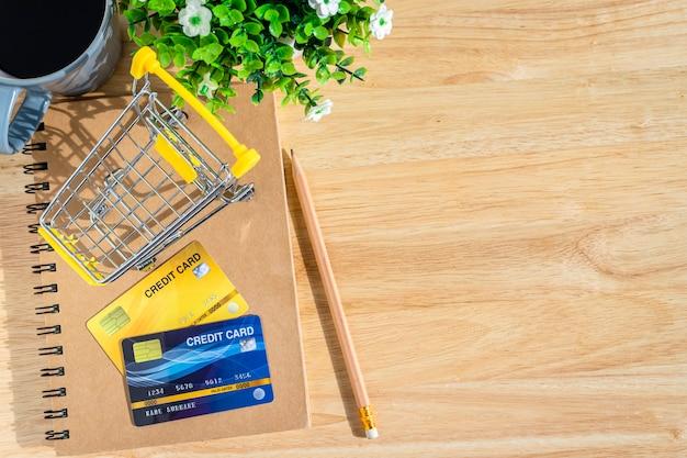 Karty kredytowe, notatnik, doniczka, wózek na zakupy i filiżanka kawy na drewnianym tle, bankowość internetowa widok z góry stół biurowy.