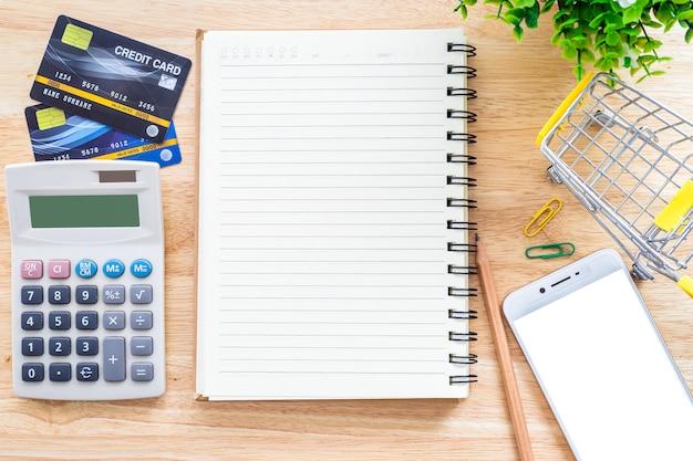 Karty kredytowe z notebookiem i kalkulator na pulpicie