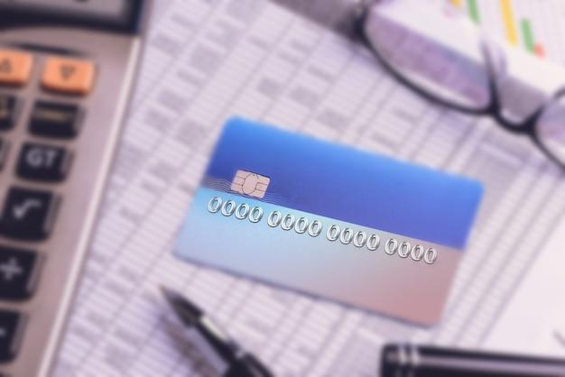 Karty kredytowe z wyciągami z kart kredytowych, konta, długopis, kalkulator i okulary