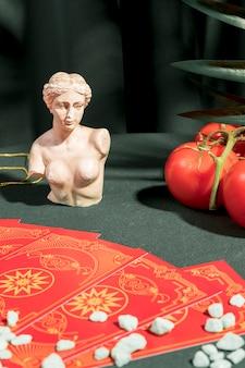Karty tarota obok popiersia i pomidorów