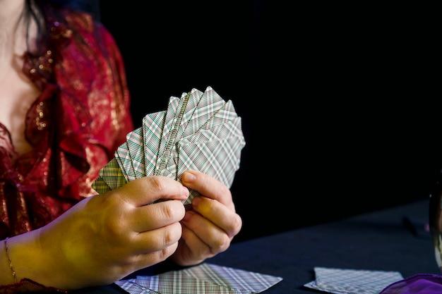 Karty w rękach wróżki w magicznym salonie