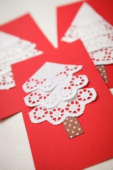 Karty wykonane ręcznie przy pomocy improwizowanych materiałów serwetek czerwonej tektury i taśmy pakowej
