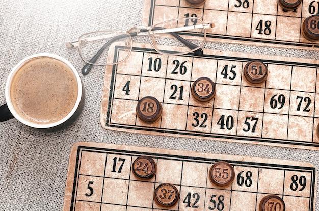 Karty z numerami i beczkami lotto. kawa i szklanki