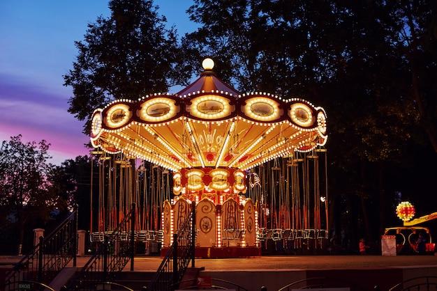 Karuzela karuzela w parku rozrywki w mieście wieczorem