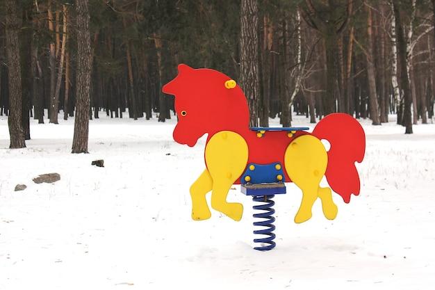 Karuzela na placu zabaw w zimowym lesie