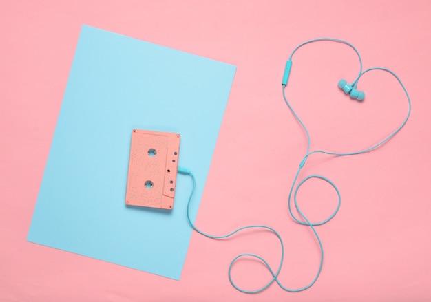 Kaseta audio i słuchawki na niebieskim różowym pastelowym tle. koncepcja miłości muzycznej. styl retro. minimalizm. widok z góry