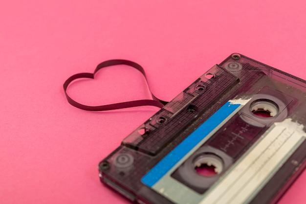 Kaseta magnetofonowa na tle róży. film kształtujący serce, pocztówka walentynkowa. pusta przestrzeń.