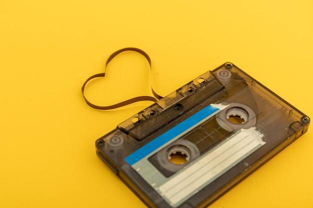 Kaseta magnetofonowa na żółtym tle. film kształtujący serce, pocztówka walentynkowa. pusta przestrzeń.