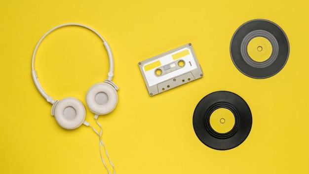 Kaseta magnetofonowa, słuchawki i płyty winylowe na żółtym tle. retro urządzenia do przechowywania i odtwarzania nagrań audio.