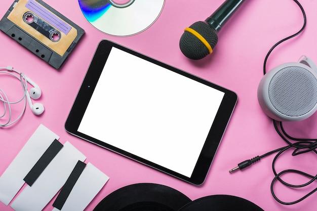 Kaseta; płyta cd; słuchawka; płyta winylowa; mikrofon; głośnik; papierowe klawisze fortepianu wokół cyfrowego tabletu na różowym tle