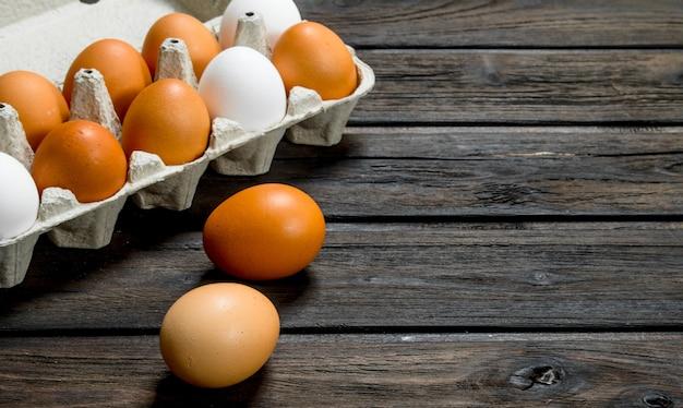 Kaseta świeżych jaj. na drewnianym tle.
