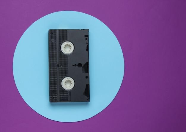 Kaseta wideo na fioletowym tle z niebieskim pastelowym kółkiem. minimalistyczna koncepcja retro. widok z góry
