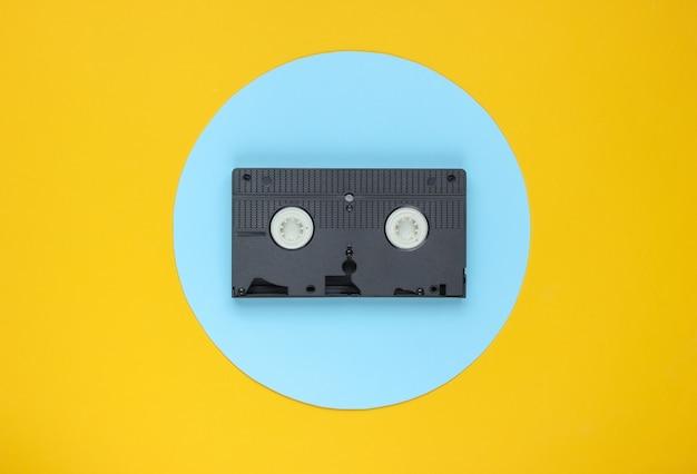 Kaseta wideo na żółtym tle z niebieskim pastelowym kółkiem. minimalistyczna koncepcja retro.