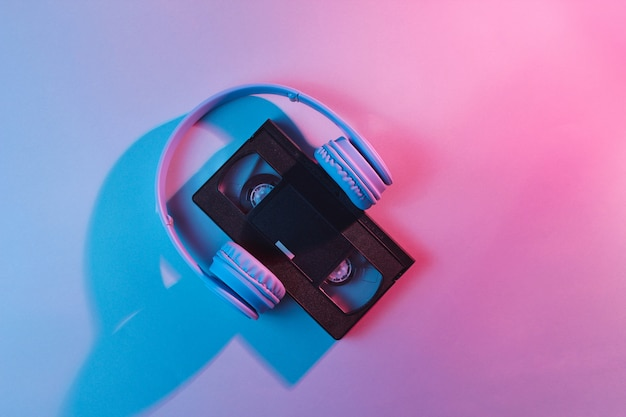 Kaseta wideo ze słuchawkami. fala retro, światło neonowe, ultrafiolet. widok z góry, minimalizm