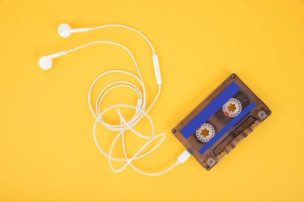 Kaseta z taśmą i białe słuchawki. kompozycja w formie odtwarzacza