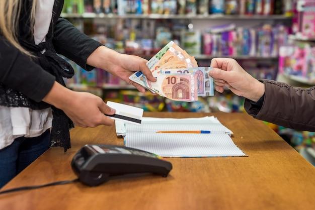 Kasjer bierze banknot euro z ręki konsumenta