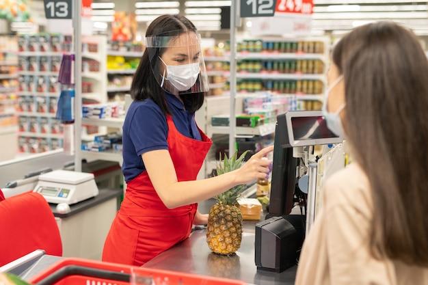 Kasjer i klient noszący osobiste maski ochronne w nowoczesnym supermarkecie podczas dni kwarantanny