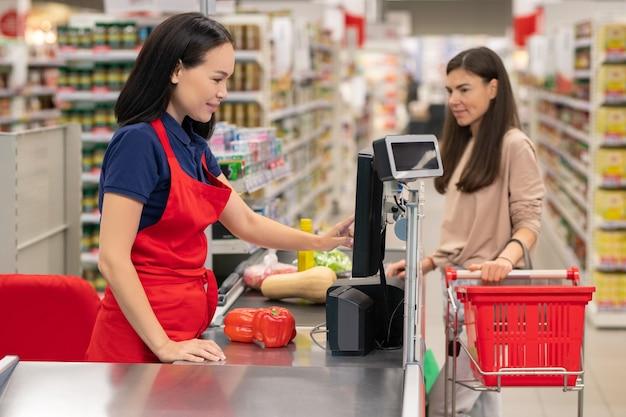 Kasjer sygnalizuje towar dla klienta przy kasie w nowoczesnym supermarkecie